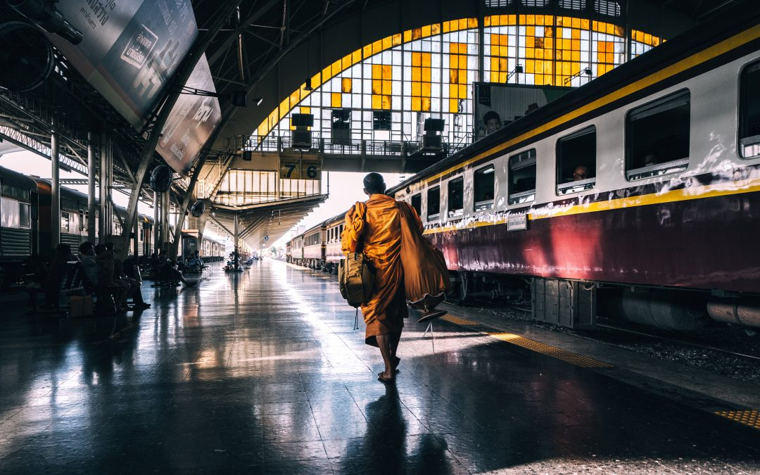A monk walks through Bangkok's old train station to catch his departure. Photo by Ryan Tang on Unsplash